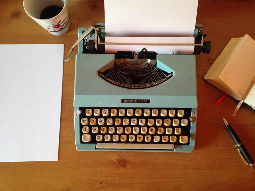typewriter with blank page on desk