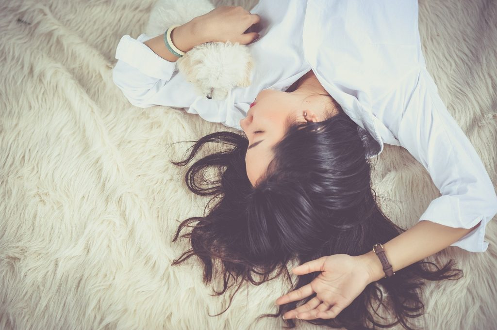 woman sleeping, holding small dog, upside down in frame