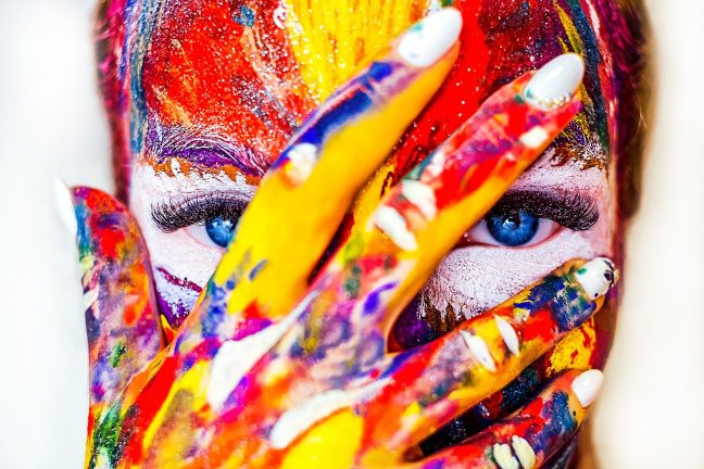 woman's face, partially obscured by hand, completely covered in multiple colors of paint