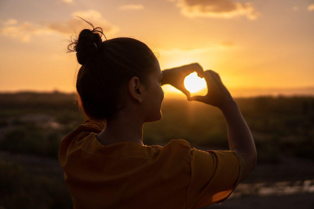 sunset through hands forming a heart