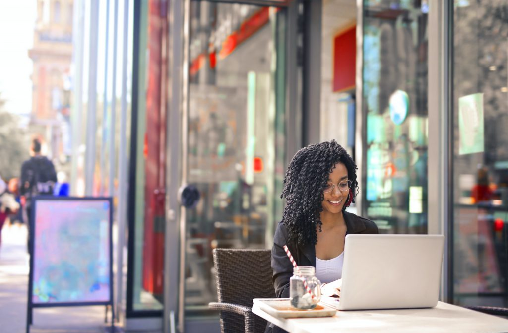 smiling woman sitting outside cafe with laptop
