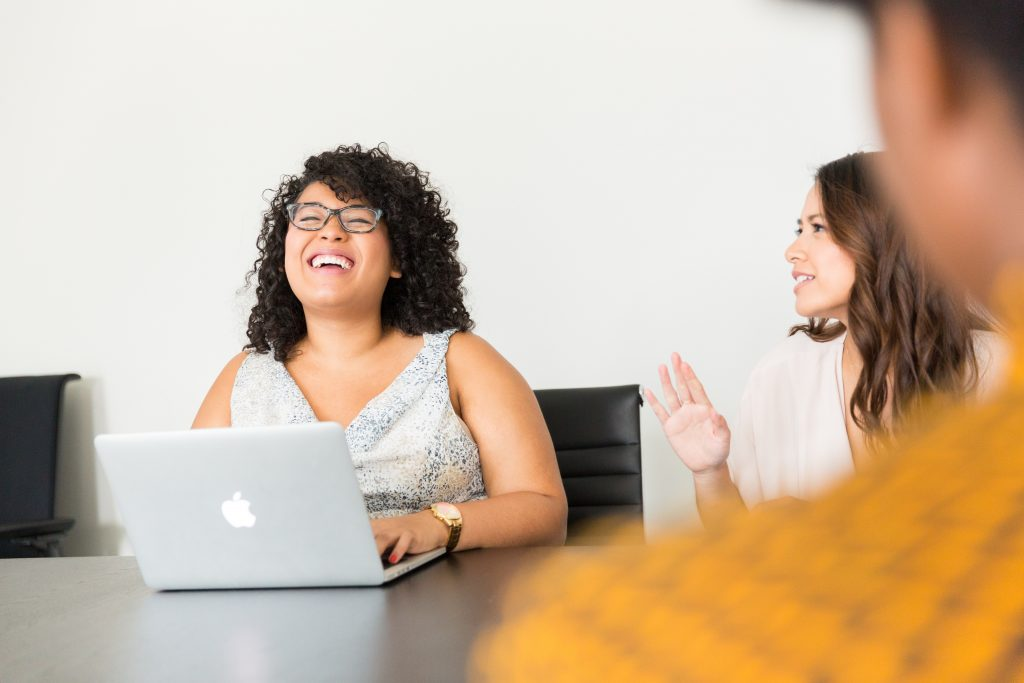 woman with laptop laughing while another woman talks